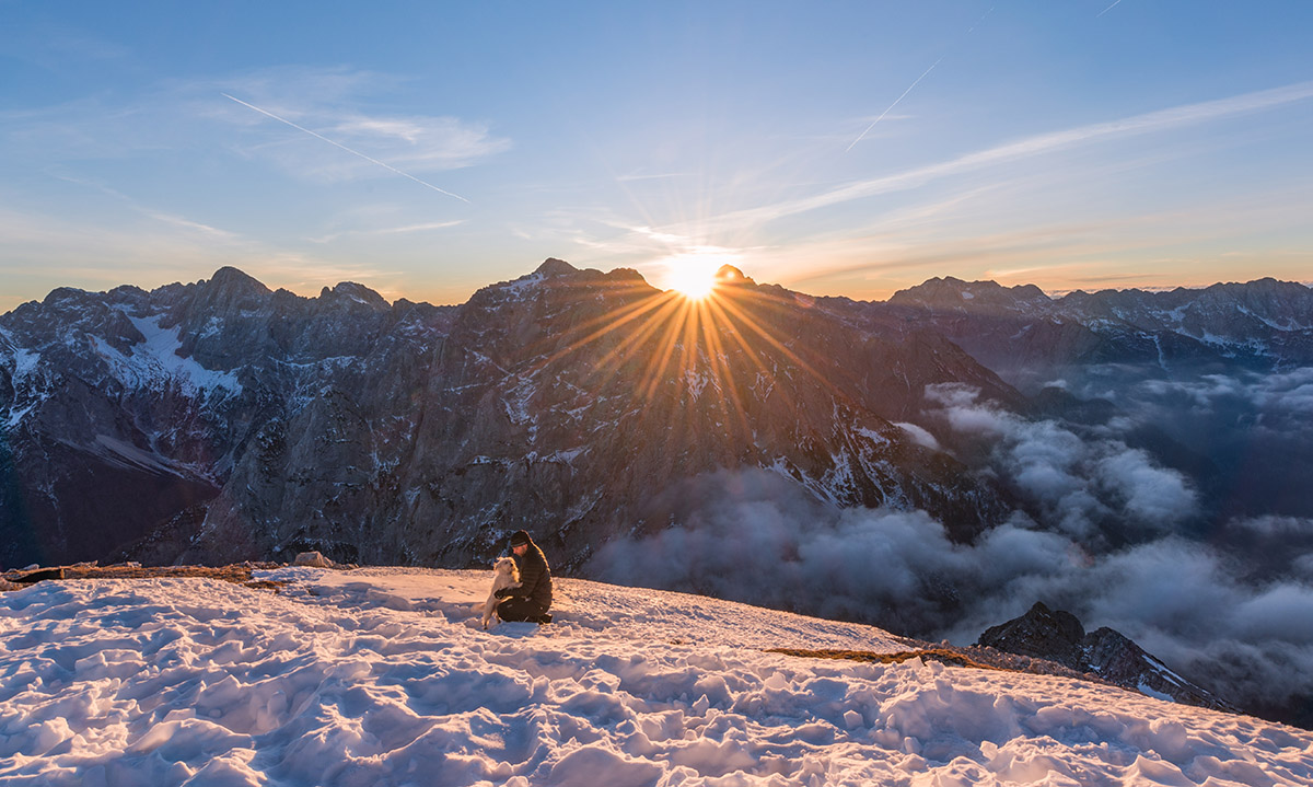 Man and dog enjoying the sunrise on top of the mountain.