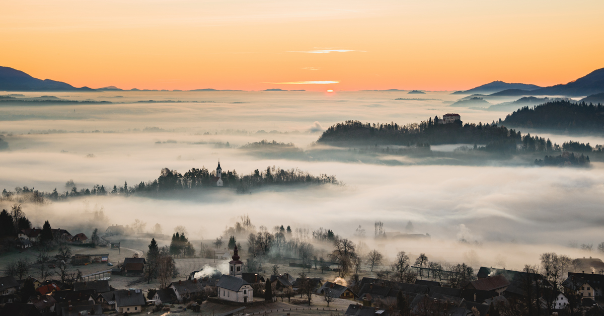 Church and villages hiding in the early morning fog. A misty sunrise in the countryside.