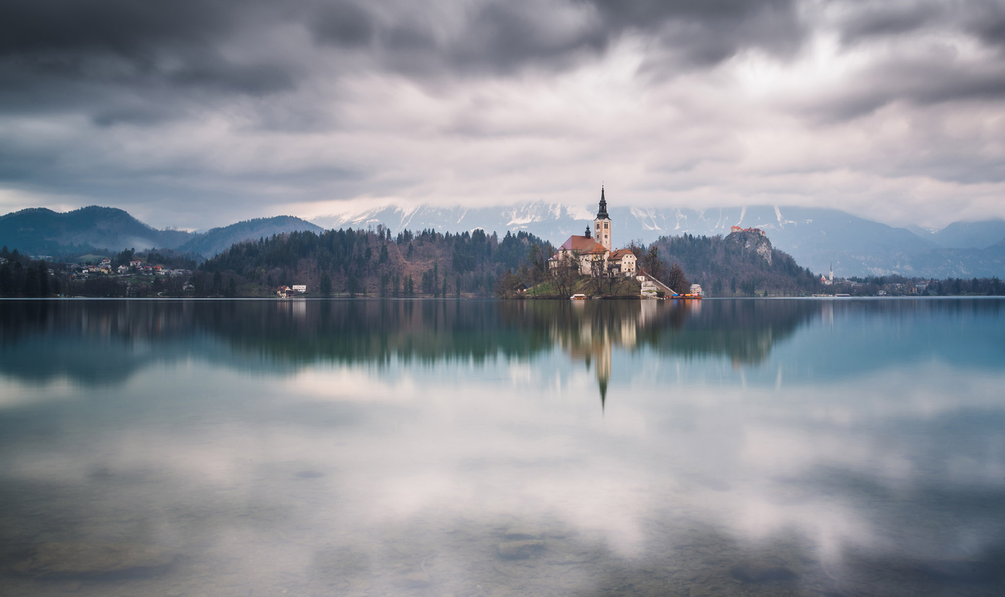 Lake Bled on a cloudy spring day with dark clouds above the landscape.