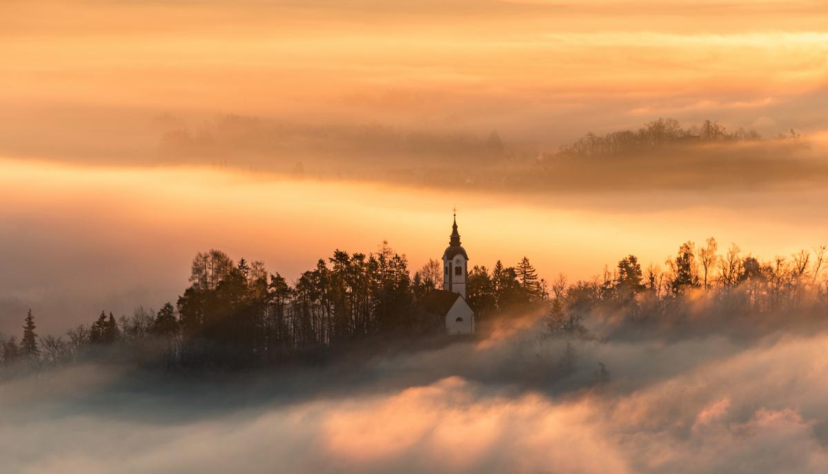 Church and castle hiding in the early morning fog. A misty sunri