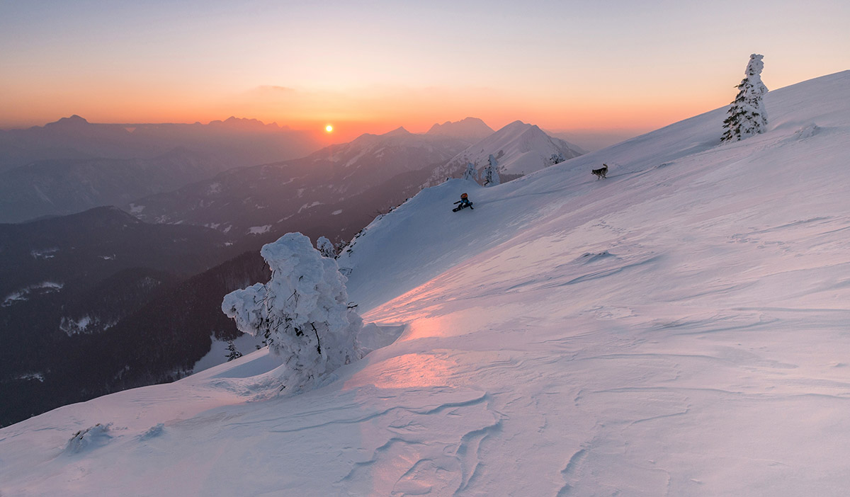 Snowboarder and his god enjoying the winter sunset
