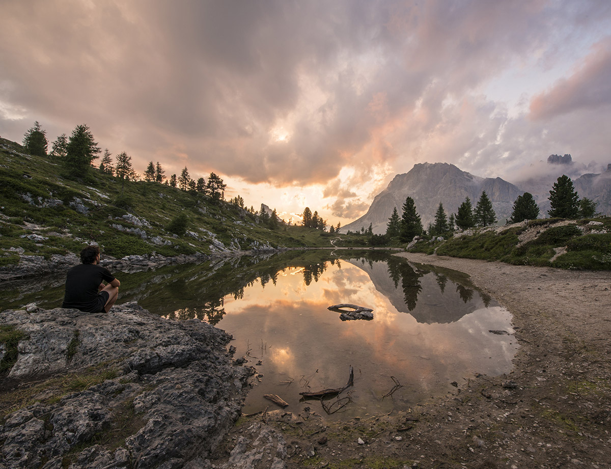Male hiker gazing at fascinating reflections of the Dolomites mo