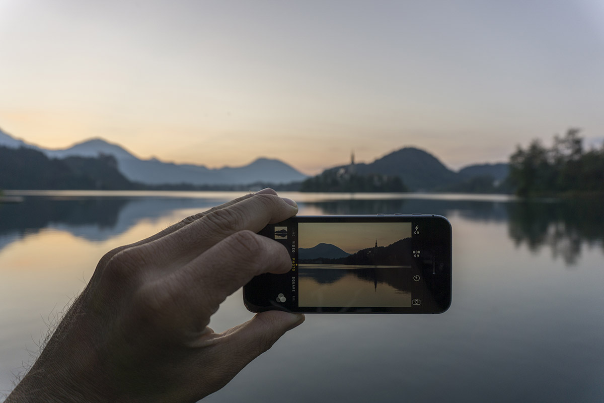 Man taking a photograph with his mobile phone at lake Bled, Slov