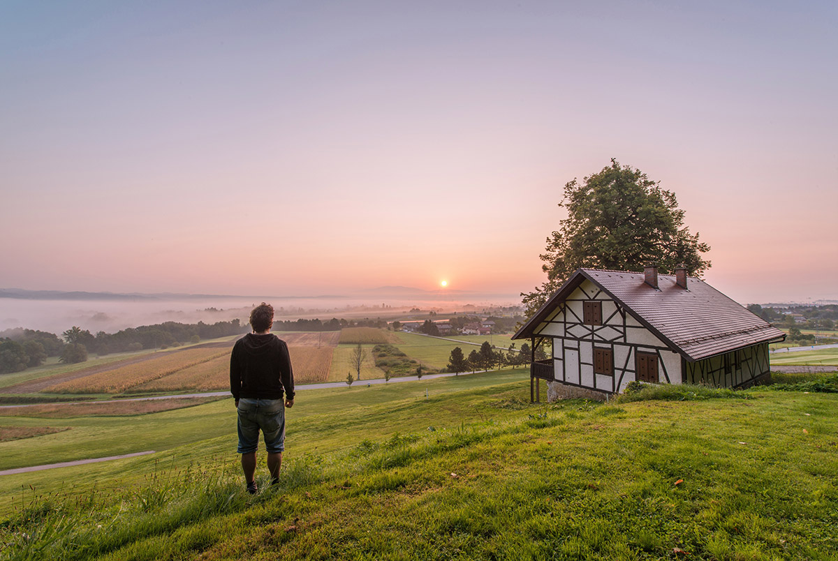 Man posing in front of beautiful sunrise by the medieval house i