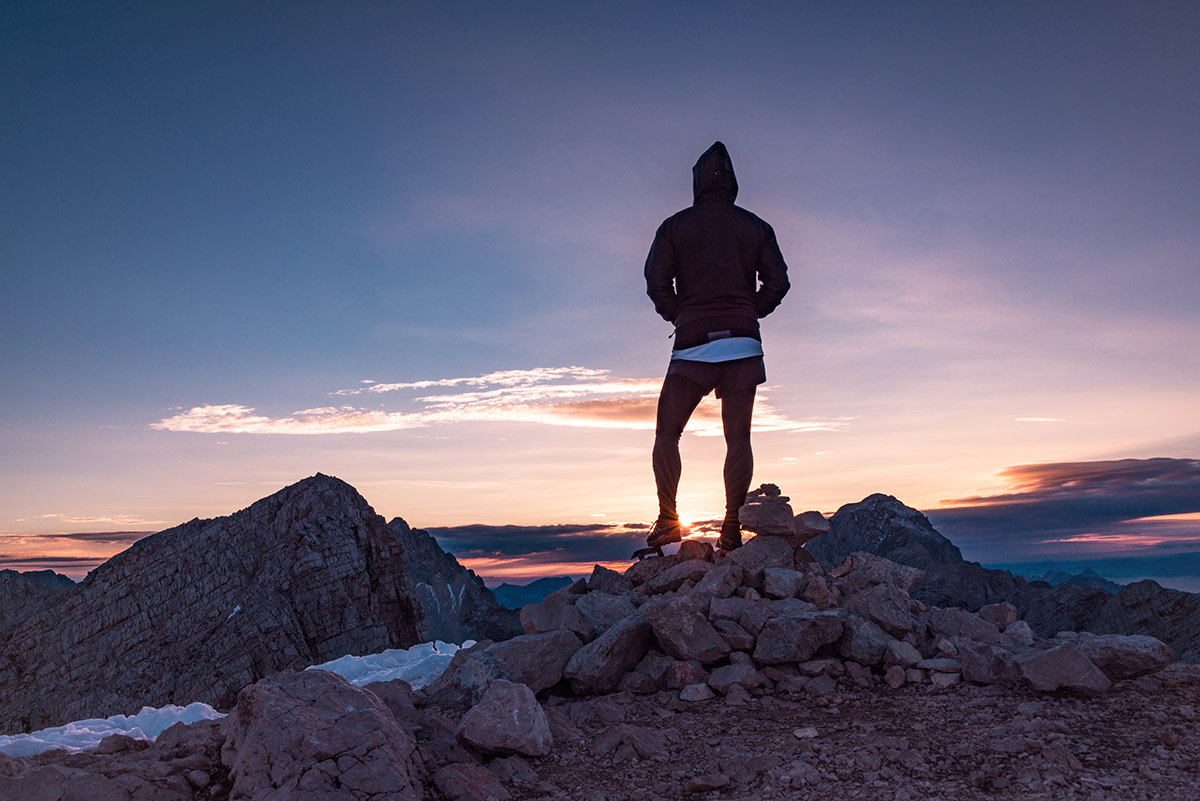 Male hiker in the vast mountain landscape at sunset. Beautiful m